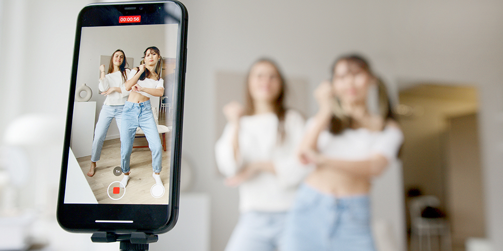 Influencer taking video on a smart phone to record dances.