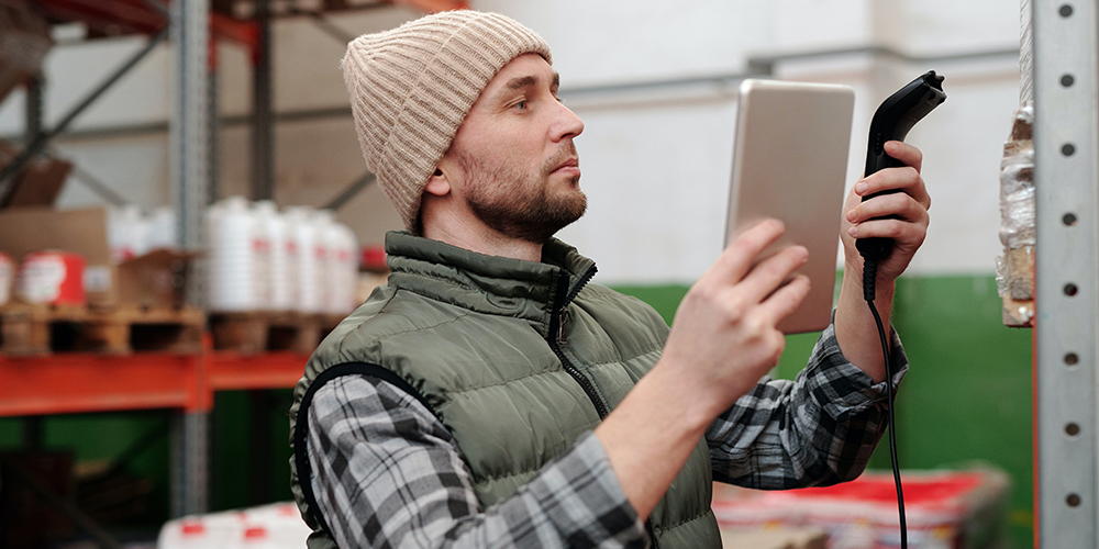 Man scanning inventory with tablet in one hand and a scanner in the other.