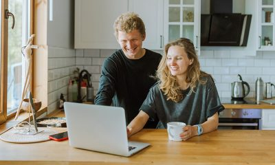 Man and woman at kitchen table online shopping on laptop together, boosting customer loyalty.