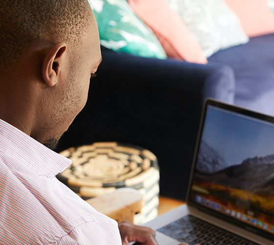 Over the shoulder view of freelance Black man working on laptop on the couch.