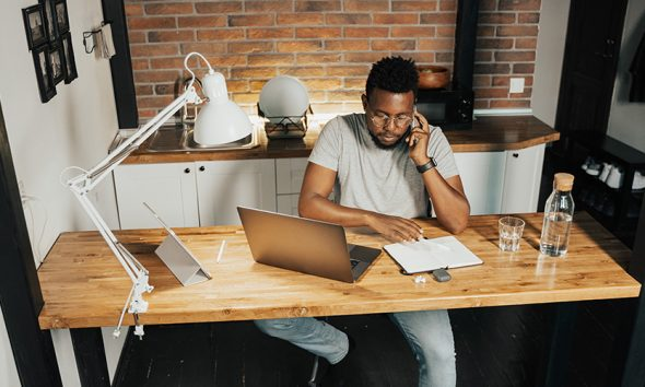Black man doing remote work at an in-home desk and laptop setup while talking on the phone.
