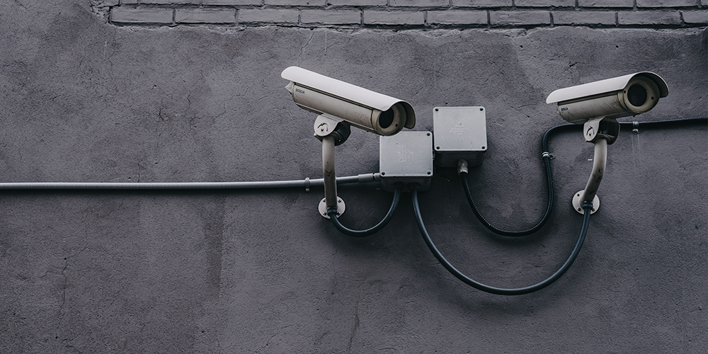 Security cameras on a gray cement wall that can be outfitted with AWS Panorama to give machine learning.