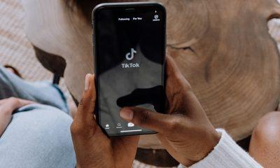 Black person's hands holding a phone loading TikTok above a wooden table.