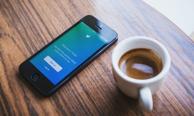Twitter open on a smartphone on table next to a cup of warm brown tea.