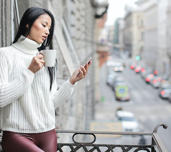 Woman checking social media on her phone on a balcony overlooking city traffic.