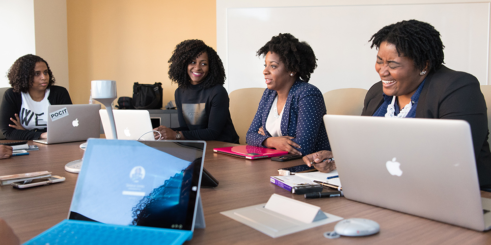 Women in a meeting around table, inclusion as a part of stopping gender discrimination.