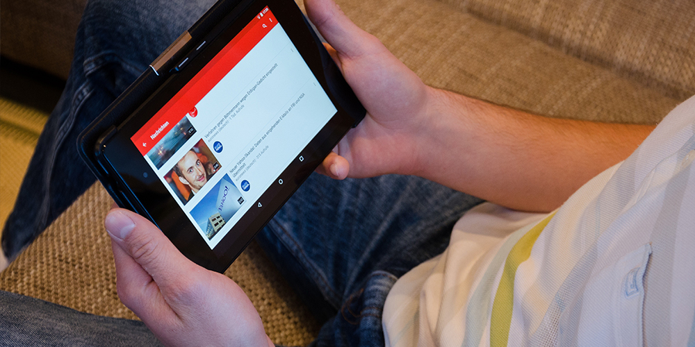 YouTube open on a tablet in lap of user on their recommended page built by the algorithm.