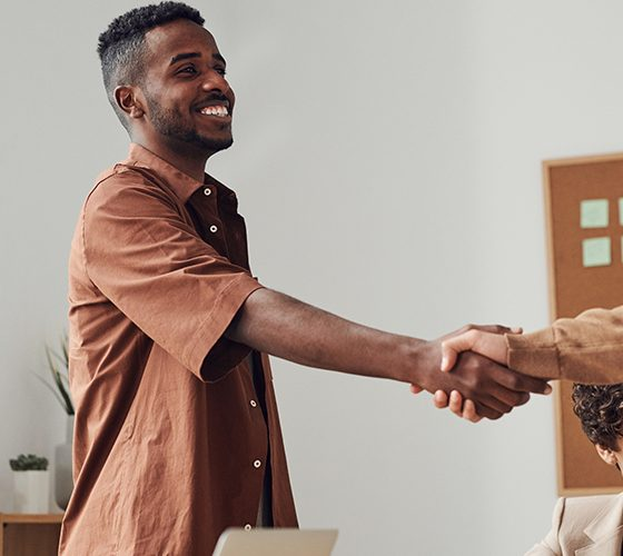 Two men standing in meeting room with others, shaking hands as they agree to be co-founder together.
