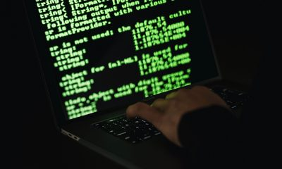 Person open on hacking computer screen, typing on keyboard.