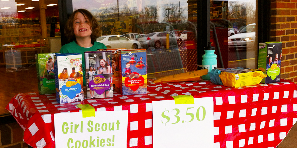 Girl Scouts table selling cookies with smiling young girl behind the table.