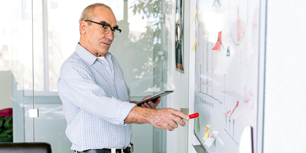 Balding man in glasses at a whiteboard, using supplies from Office Depot.