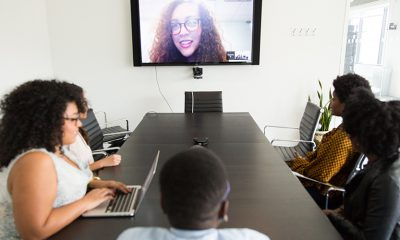 Remote teams having a meeting with some of the team in the room around a table, others on a large screen.