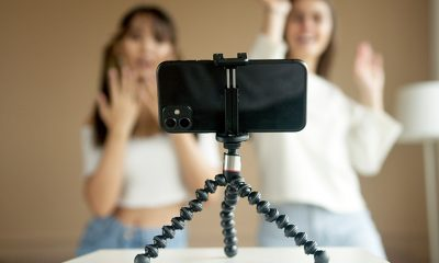 Phone camera on stand in foreground with two women filming for TikTok or Instagram reels in the background