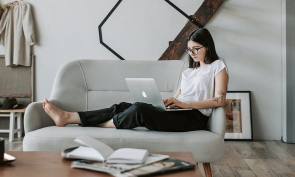 Woman working remotely on her couch with a laptop on her lap.