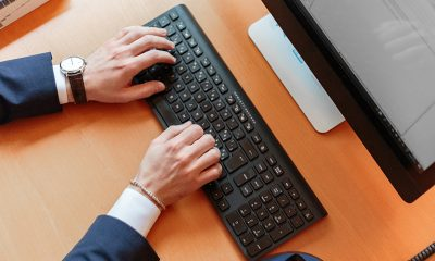 Person using content management system with hands on keyboard and small bit of desktop visible.