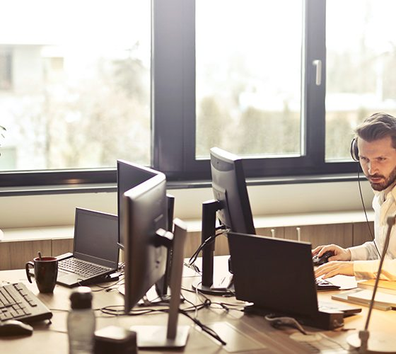 Man working in office with headphones on, making use of flexible four-day workweek.