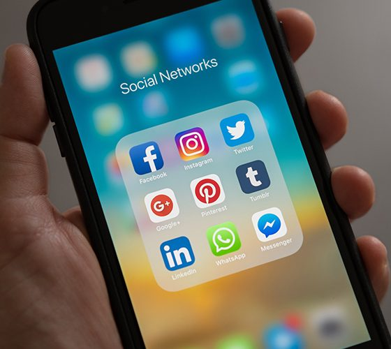 Twitter and other social media apps open on a phone being held in a hand. Will they go to a paid option subscription model?