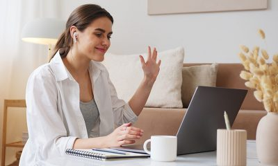 Woman waving at laptop in living room, on team building activity.