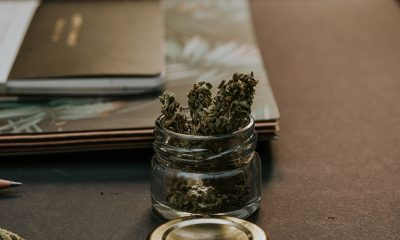 A small jar of cannabis on a desk with notebooks, sold online in a nicely made jar.