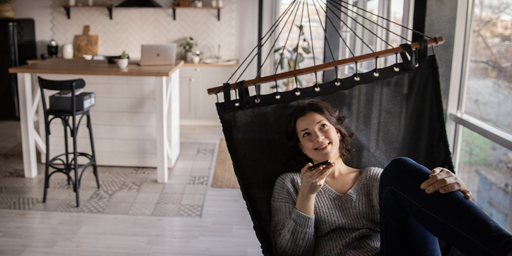 Woman in a hammock in a kitchen, talking on the phone using Clubhouse app.