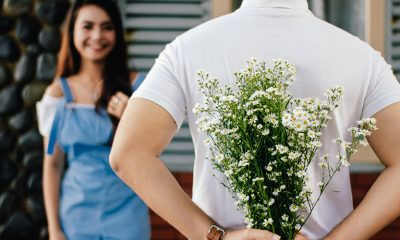 Man holding flowers behind his back while woman in background smiles. Background checks can ensure a safe modern dating experience.