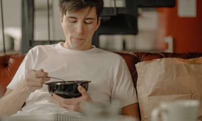 Man seated on couch eating food from a food delivery person.