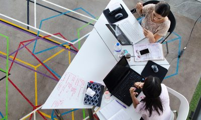Birds eye view of two women networking at a table with colorful interconnecting pattern on a concrete floor.