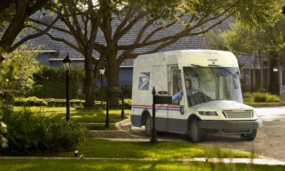 New USPS truck in a fictional neighborhood delivering mail.