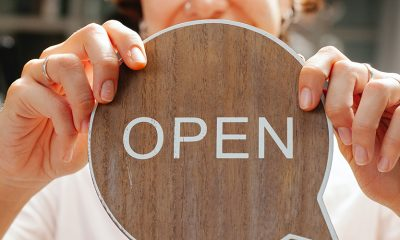 Open business sign being held by business owner for marketing purposes.