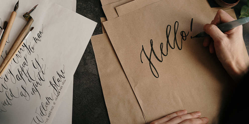 "Small business owner drawing calligraphy ""Hello!"" on brown paper sourced from Paper Source."