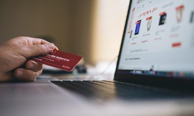 Ecommerce site open on a laptop with a hand holding a credit card next to the screen for shopping.