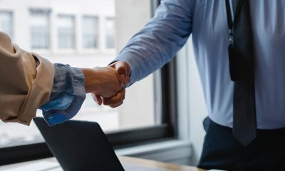 Two business partners shaking hands as part of a Tiger Global acquisition deal.