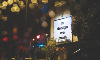 "A white sign in an urban setting reading ""In Design We Trust"" with glowing yellow lights above."