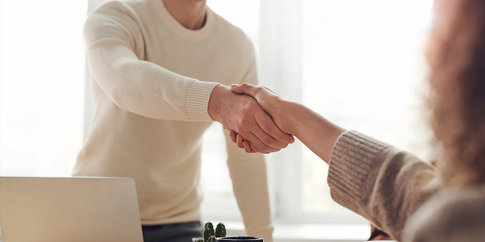 Two people shaking hands across the table, taking the opportunity to change jobs.