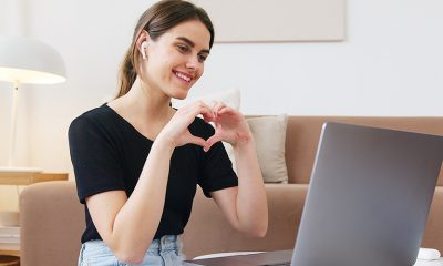 Woman forming hands into heart shape at laptop hosting live video chat, similar to Facebook's new app Hotline