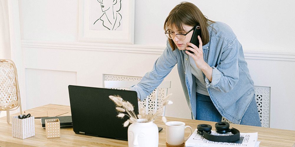 Amazon sellers leaned over a laptop while on the phone, checking data mid-conversation.