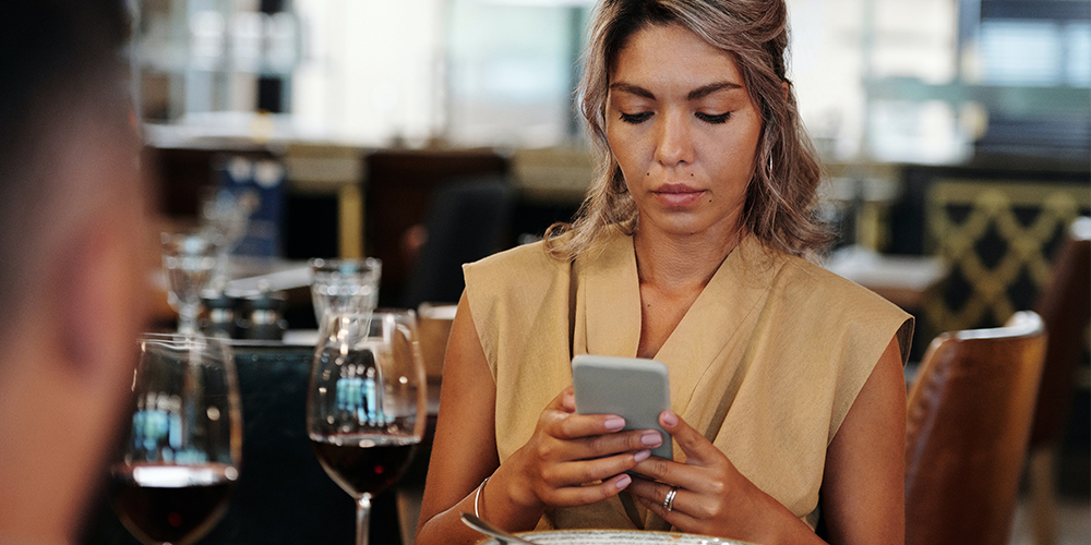 Woman checking phone as spammer acquires information.