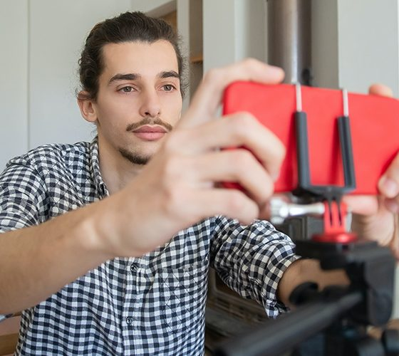 Man in front a red smartphone on a stand, setting up for a live stream.