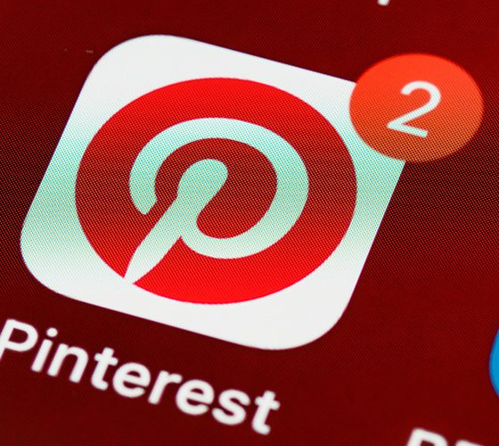 Pinterest icon on phone with 2 notifications, indicating new code of conduct.