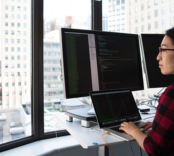 Quantum developer looking out of the window with a three monitor setup open to various coding programs.