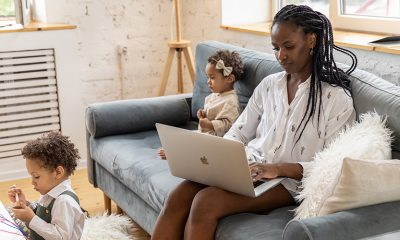 A working parent with two children playing near the couch while they update their career gaps profile.