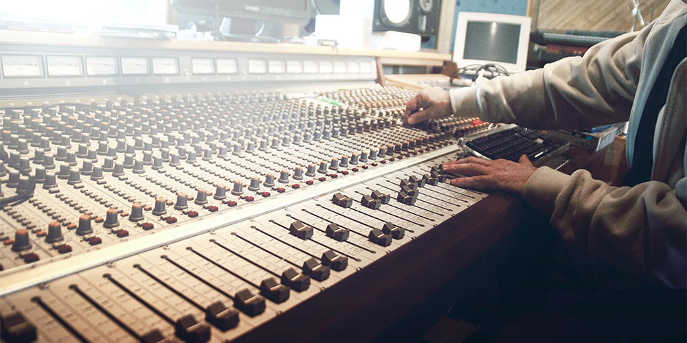 Person at audio mixing table, preparing audio branding