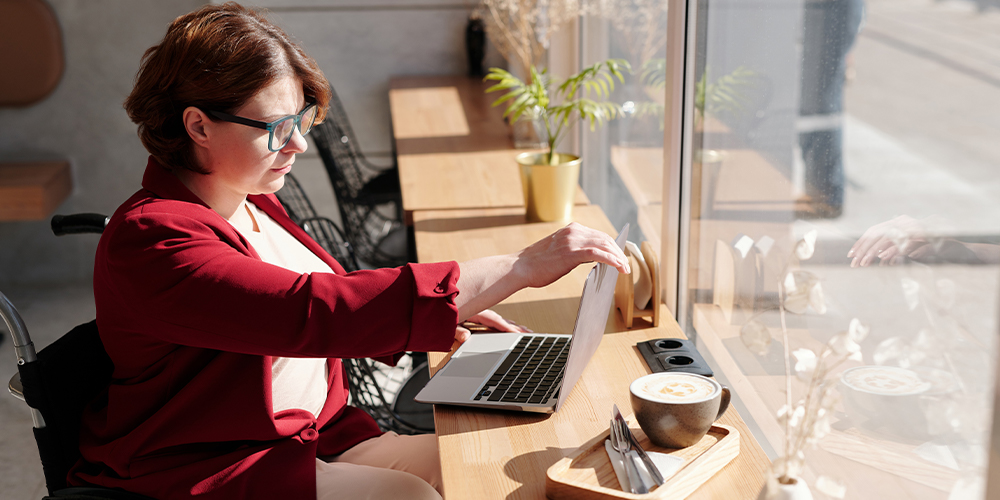 Woman in wheelchair working at laptop for her tech jobs in a bright sunny cafe