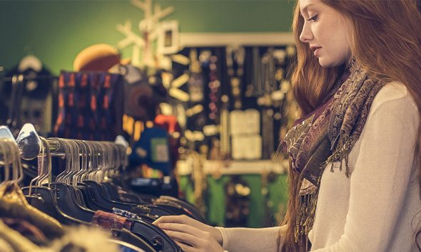 Woman looking at a rack of clothes in a second hand thrift store