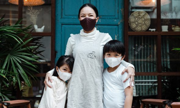 Woman in front of small business with two children, all wearing face masks