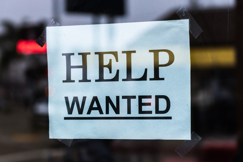"""White paper sign with black text reading """"Help Wanted."""""""