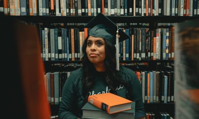 African American woman in library with two books and graduation cap.