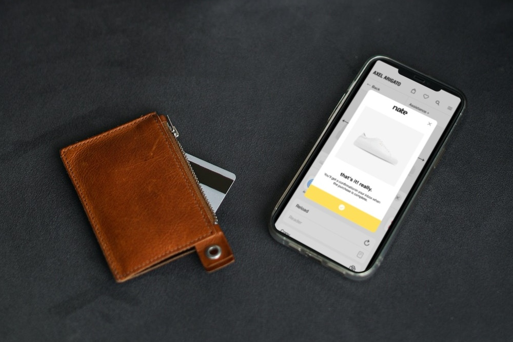 Brown leather wallet with tip of credit card sticking out next to a iPhone showing a shoe purchase on the Nate App.