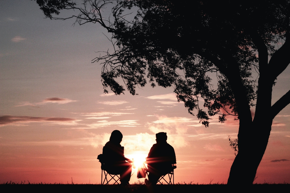 Two silhouettes of people looking out over the sunset
