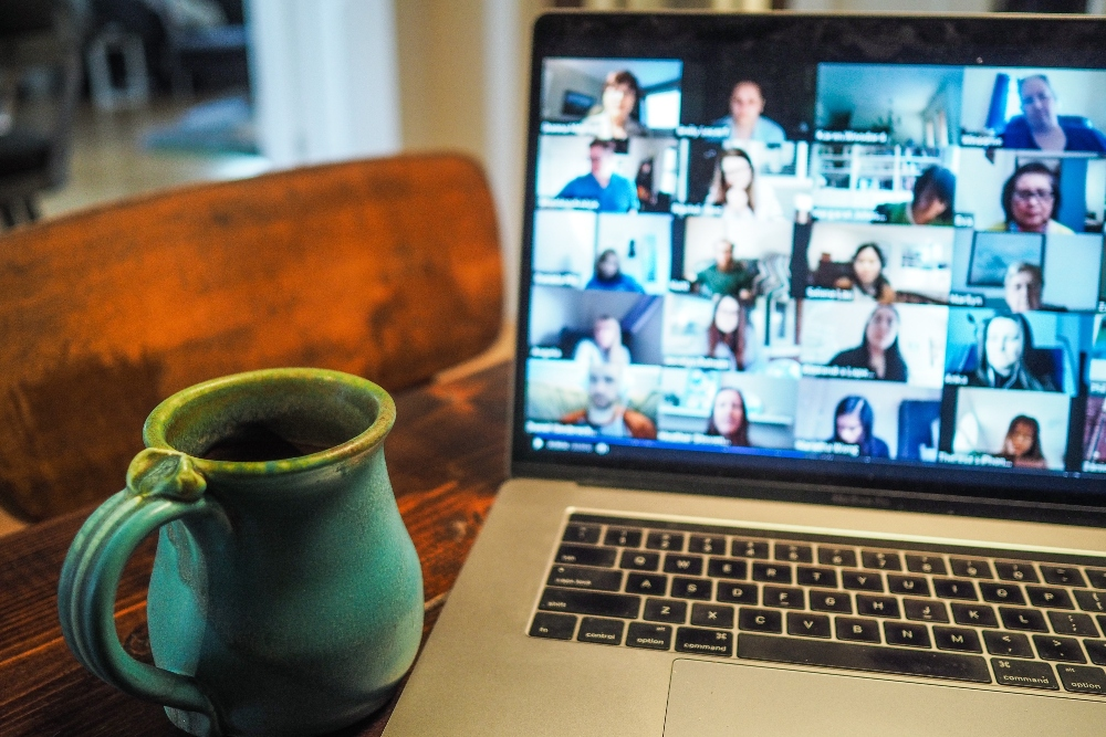 Multi-member Zoom call on a Apple Mac laptop with a blue mug of black coffee next to it.